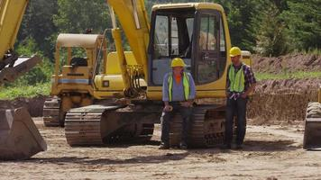 Two blue collar workers talking by excavation machinery video