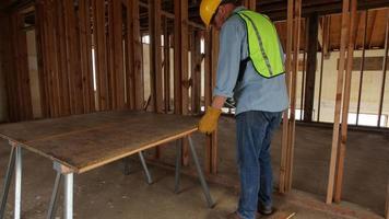 Trabajador de la construcción cortando madera contrachapada con sierra video