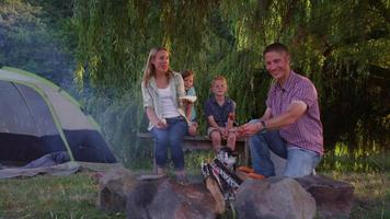 Family roasting hot dogs at camp site video