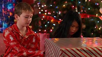 Two kids tear paper off Christmas gifts video