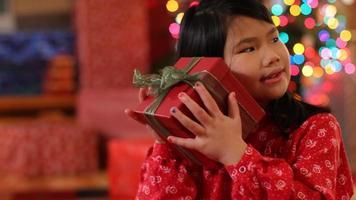 Young girl shaking Christmas gift video