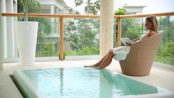 une femme utilise une tablette numérique au bord de la piscine au tropical resort video