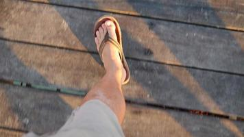 Looking down at feet in sandals walking on pier video