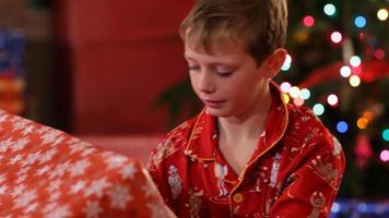 Boy shaking and listening to Christmas gift video