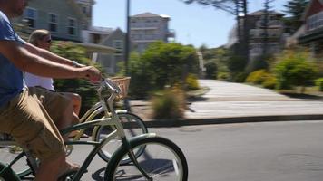 casal andando de bicicleta em comunidade costeira de férias video