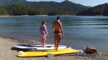 pareja, con, stand up paddle, tablas, por, lago video