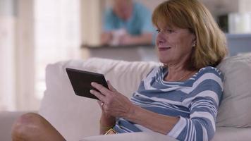 Senior woman in living room using digital tablet video