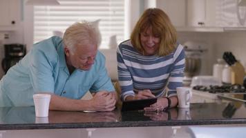 Senior couple using digital tablet together video