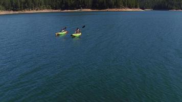 tiro aéreo de drone de casal andando de caiaque no lago video