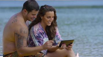 pareja sentada junto al lago con tableta digital video