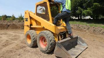Worker driving excavator video