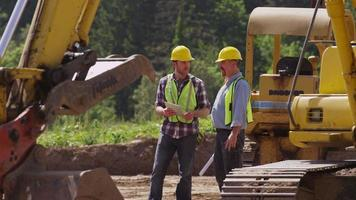 Two workers talking by machinery video