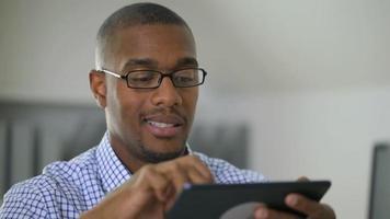 Businessman using digital tablet in office video