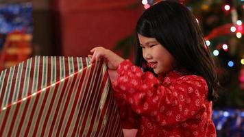Young girl tearing paper off Christmas present video