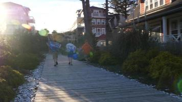 Three boys run up wooden pathway to beach video