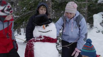 Mother and kids working on snowman together video