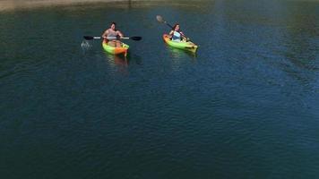 Aerial drone shot of couple kayaking on lake video