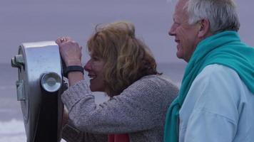 Senior couple at beach looking through viewer video