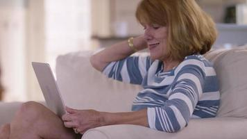 Senior woman in living room using laptop computer video