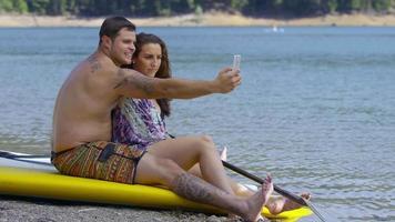 Pareja sentada junto al lago con tablas de paddle surf tomando selfies video