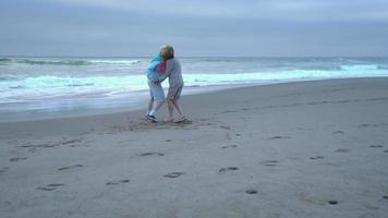 Senior couple dancing and playing at beach video
