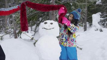 Two children building snowman together video