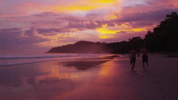två barn springer på stranden i solnedgången video