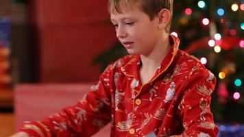 Boy tearing paper off Christmas gift video