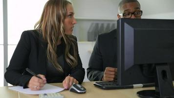 Businessman and businesswoman working together on computer in office video