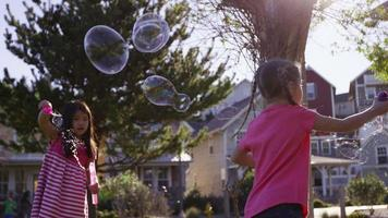 Girls blowing bubbles at park video