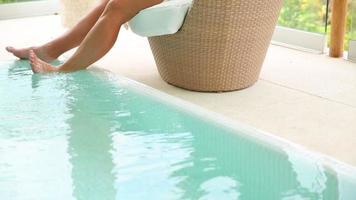 Woman uses digital tablet by pool at tropical resort video