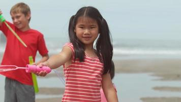 Children blowing bubbles at the beach slow motion video