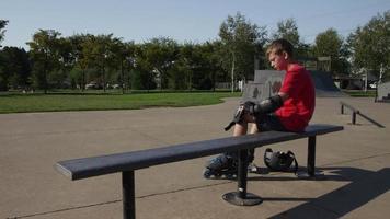jongen krijgt veiligheidsuitrusting bij het voorbereiden om te skaten in het park video