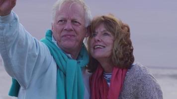 casal sênior tirando uma selfie na praia video