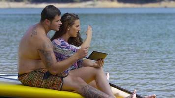 Par sentarse junto al lago con tablas de paddle surf con tableta digital video
