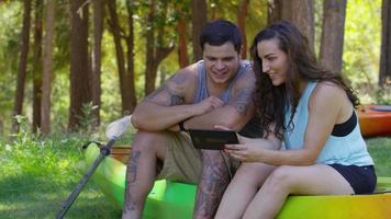 casal com caiaques usando tablet digital video