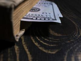 Old book and two hundred dollars bookmark in a thick book photo