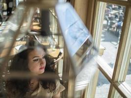 cute girl with curly hair sits at a table in a cafe photo