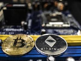 Coins of ethereum and bitcoin on the background of the chip photo