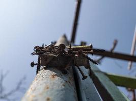 rusty screws on the magnet on the iron pillar on the street photo