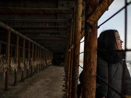 young girl in a coat stands near metal rusty structures photo