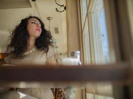 girl sits at a table in a cafe and looks out the window photo