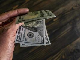 Close up of male hand holds two banknotes of hundred dollars photo