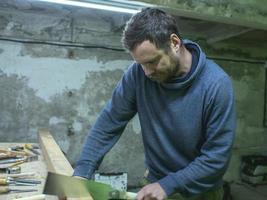 woodworker with a beard sawing a wooden beam with a hand saw photo