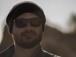 portrait of a stylish man with a beard in a knitted hat and sunglasses photo