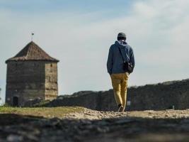 un hombre con un suéter con capucha y un gorro de punto está caminando por la carretera foto