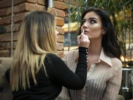 the make up artist does make up to the beautiful young woman photo