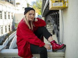 blonde girl sitting under a bridge photo