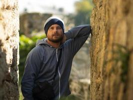 man in knitted hat and jacket with hood posing in a ravine photo