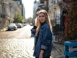 beautiful blonde girl stands in an old alley in a denim jacket photo